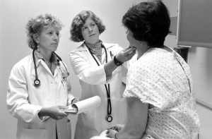 Two doctors in white coats examining a patient